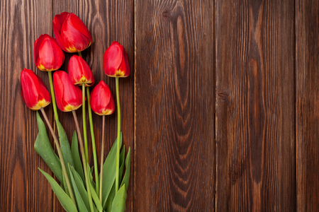 red tulip: Red tulips bouquet over wooden table background with copy space Stock Photo