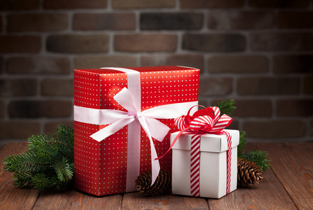Christmas gift boxes and fir tree branch on wooden table Stock Photo