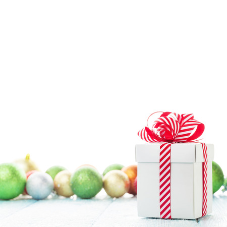 christmas gift box: Christmas gift box and colorful baubles decor on wooden table. Isolated on white
