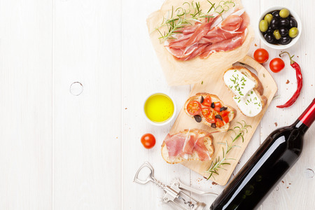pan y vino: Bruschetta with cheese, tomatoes and prosciutto on cutting board. Top view with copy space Foto de archivo