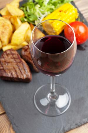 copa de vino: Vidrio de vino rojo y carne a la parrilla con patatas, ma�z, ensalada en placa de piedra