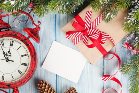gift box: Christmas greeting card over wooden background with snow fir tree, alarm clock and gift box Stock Photo