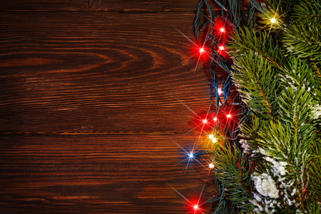 colorful lights: Christmas tree branch and colorful lights on wooden background. View with copy space Stock Photo