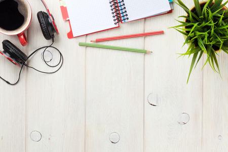 メモ帳、コーヒー カップとヘッドフォンでオフィスの木製デスク。コピー スペース平面図