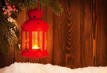 christmas candle: Christmas candle lantern on fir tree branch in snow. View with copy space