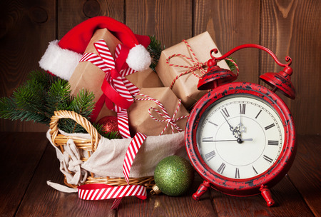 gift box: Christmas gift boxes and fir tree branch in basket with alarm clock