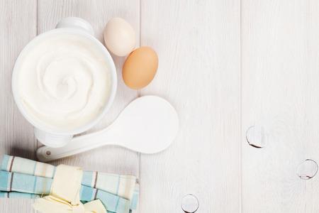 ボウルと卵が木製のテーブルの上にサワー クリーム。コピー スペース平面図 写真素材