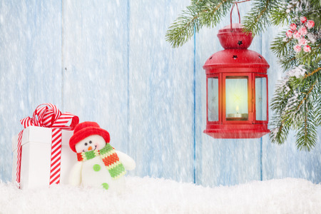 snowman wood: Christmas candle lantern, gift box and snowman toy in snow. View with copy space