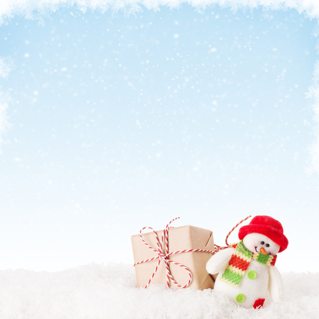 Christmas gift box and snowman toy in snow with background for copy space