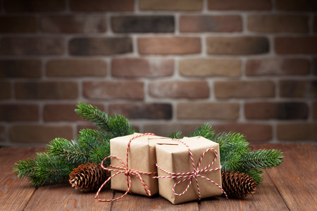 Christmas gift boxes and fir tree branch on wooden table. View with copy space