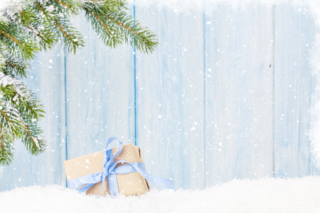christmas tree branch: Christmas gift box and fir tree branch in snow. View with copy space