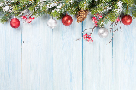 snow tree: Christmas wooden background with snow fir tree and decor Stock Photo