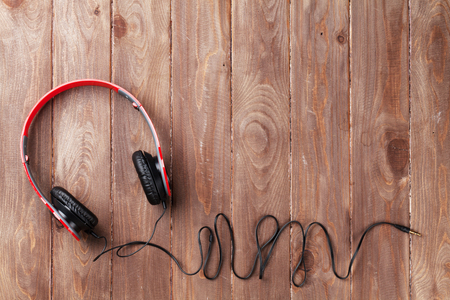 modern background: Headphones on wooden desk table. Music concept. Top view with copy space Stock Photo