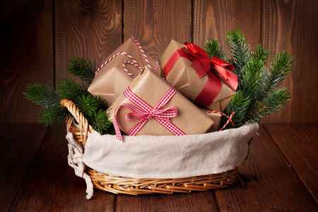 basket: Christmas gift boxes and fir tree branch in basket on wooden table
