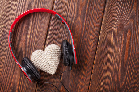 radio dj: Heart toy with headphones on wooden table with copy space. Valentines day concept. Stock Photo