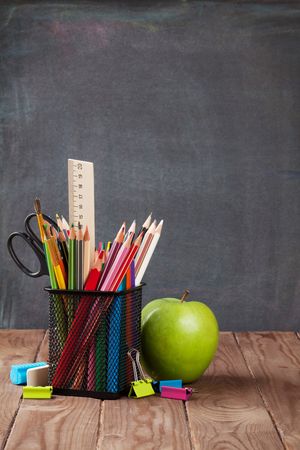chalk board background: School and office supplies and apple on classroom table in front of blackboard. View with copy space
