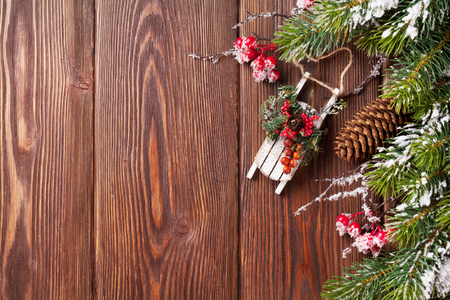 madera r�stica: Christmas wooden background with snow fir tree and holly berry
