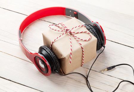 Geschenk-Box mit Kopfhörern auf Holztisch Standard-Bild