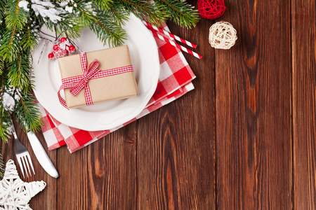 dining: Christmas table setting with gift box and fir tree on wooden table. Top view with copy space