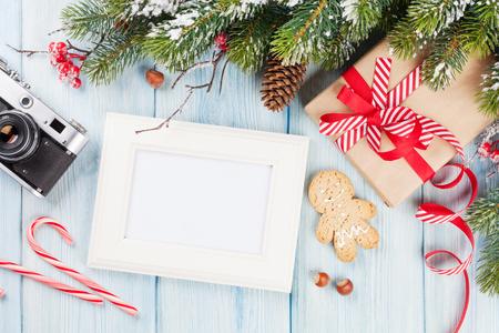 cajas navide�as: Marco de fotos de Navidad en la mesa de madera con el �rbol, c�mara y caja de regalo. Vista superior con espacio de copia Foto de archivo