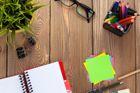phonebook: Office table with flower, blank notepad and colorful pencils. View from above with copy space