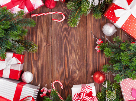candy border: Christmas gift boxes, decor and fir tree branch on wooden table. Top view with copy space Stock Photo