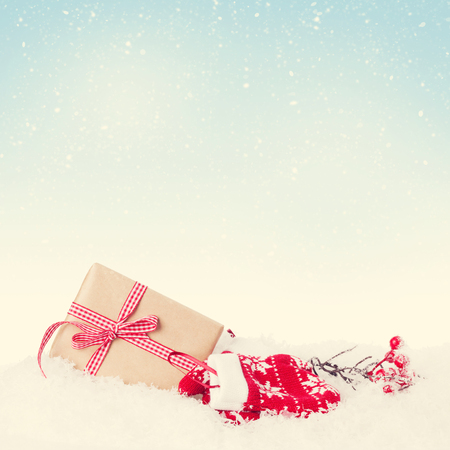 sky: Christmas gift box in snow with background for copy space. Retro toned