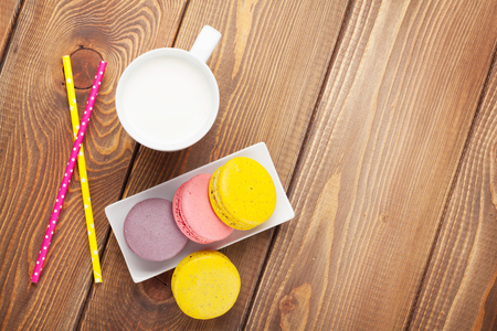 assorted: Colorful macaron cookies and cup of milk on wooden table background with copy space