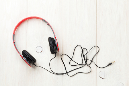 headphones: Headphones on wooden desk table. Music concept. Top view with copy space Stock Photo