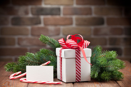 card: Christmas gift box, greeting card and fir tree branch on wooden table Stock Photo