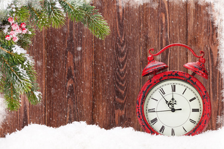 Christmas fir tree and alarm clock in snow