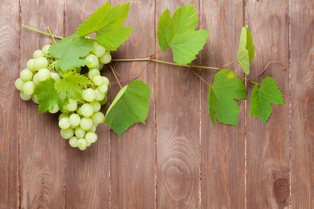 vid: Racimo de uvas y la vid en el fondo mesa de madera con espacio de copia