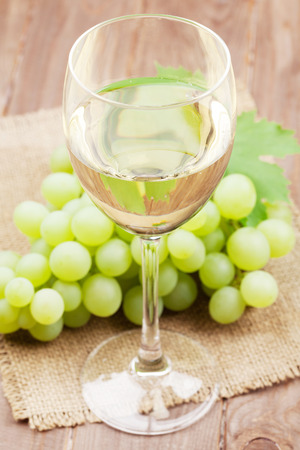wine glasses: White wine glass and grapes on wooden table