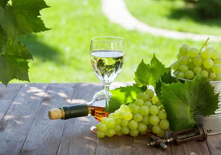 bouteille de vin: Bouteille de vin blanc et de verre avec raisin blanc sur la table de jardin Banque d'images