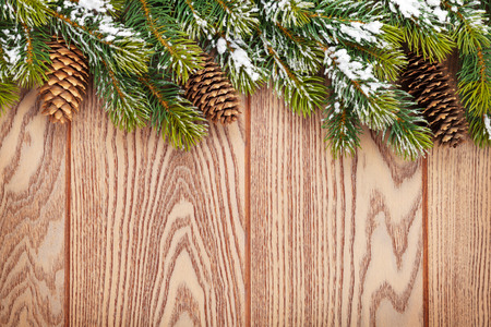 textured background: Christmas wooden background with snow fir tree and pinecones