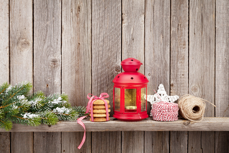shelf ice: Christmas candle lantern, gifts and decor in front of wooden wall with copy space