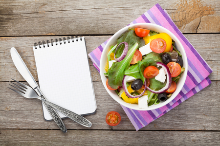 comidas saludables: Fresh healthy salad and notepad for copy space and silverware on wooden table. View from above