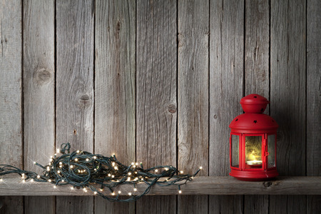 christmas light: Christmas candle lantern and lights in front of wooden wall with copy space Stock Photo