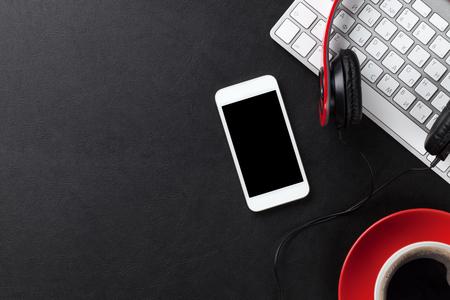 auriculares: Mesa de cuero de la oficina con la taza de café, ordenador, teléfono inteligente y los auriculares. Vista superior con espacio de copia