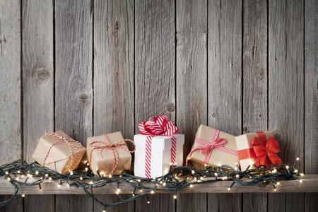 cajas navide�as: cajas de regalo de Navidad y luces en frente de la pared de madera con espacio de copia