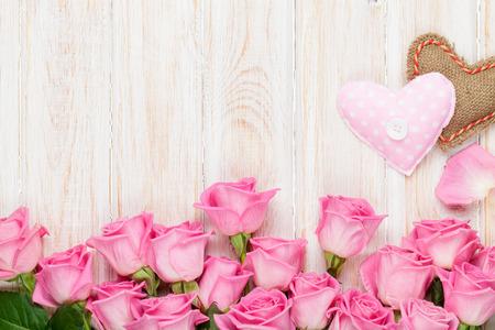 Valentinstag-Karte mit rosa Rosen und handmaded Spielzeug Herzen über Holztisch. Ansicht von oben mit Kopie Raum