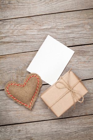 Valentines day toy heart, blank greeting card and gift box over wooden table background