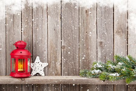 christmas decor: Christmas candle lantern and decor in front of wooden wall with copy space