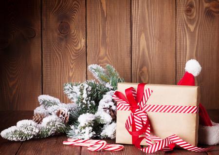 ribbon: Christmas gift box and santa hat on wooden table