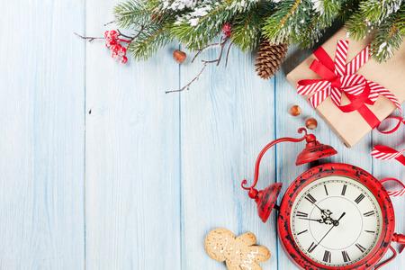 Weihnachtsgeschenkkasten, Wecker und Tanne Zweig auf Holztisch. Ansicht von oben mit Kopie Raum