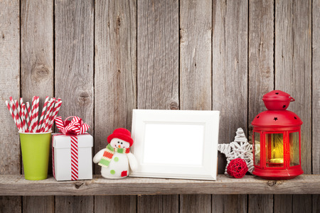 photo frame: Christmas candle lantern, photo frame and decor in front of wooden wall with copy space Stock Photo