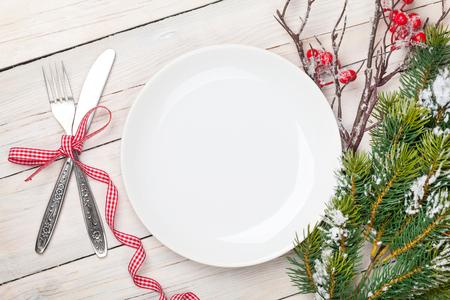 Leere Teller, Besteck und Weihnachtsbaum. Blick von oben über weißen Holztisch Hintergrund