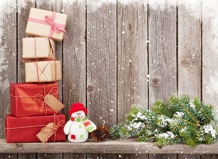 shelf ice: Christmas gift boxes and snowman toy in front of wooden wall with copy space