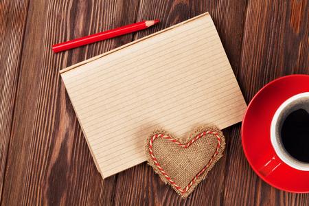 バレンタインデー グッズ中心、コーヒー カップおよびテキストのメモ帳。木製テーブルのトップ ビュー 写真素材
