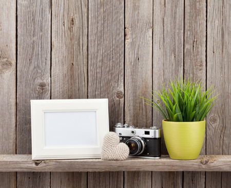 blank photo: Blank photo frame, heart gift, camera and plant on shelf in front of wooden wall Stock Photo